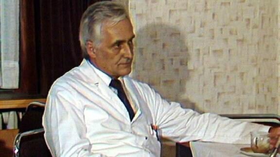 Vor einem Mann im Arztkittel steht eine Tasse auf einem Tisch