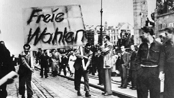 Aufstand des 17. Juni 1953 in Ostberlin. - Demonstranten tragen Plakate mit der Forderung nach freien Wahlen durch die Strassen.