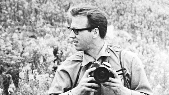 Fotograf Billhardt mit umgehangener Kamera in einem Feld, im Hintergrund Zugwaggons