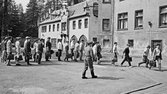 Jugendliche mit Taschen bei der Ankunft auf dem Jugendwerkhof Wolfersdorf