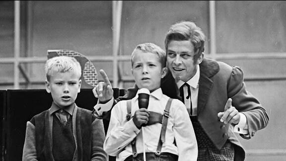 """Die DDR-Kinderfernseh-Figur """"Meister Nadelöhr"""", dargestellt von Schauspieler Ekkehard Friedrichson, mit zwei Jungen"""