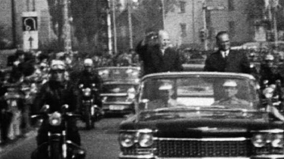 Limousine mit stehenden, winkenden Politikern