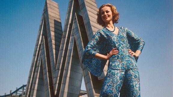 Ein Model posiert in modischem Outfit, bestehend aus einer Bluse mit weiten Ärmeln und einer Pumphose, vor dem Doppel-M auf dem Leipziger Messegelände.