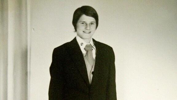Lächelnder Junge mit dunkelblauem Jacket, grauer Hose, Hemd und Krawatte.