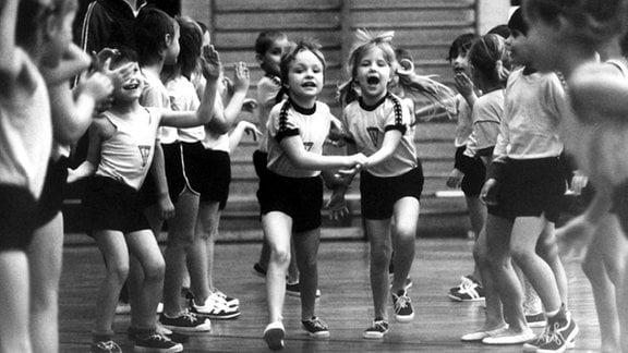 Mit Schwung durch die Gasse. Schüler der ersten Klasse der Käte-Duncker-Oberschule in Berlin-Friedrichshain am 1. Februar 1989 beim Sportunterricht in der Halle.