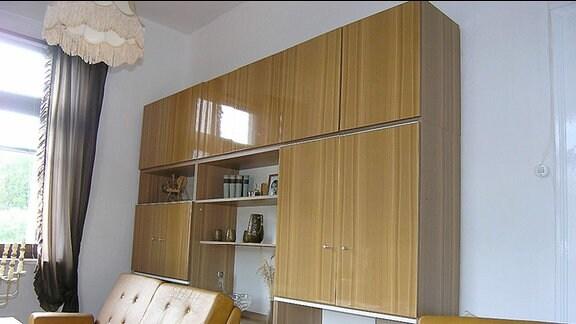 Ein Wohnzimmer mit heller Anbauwand, Lampenschirm mit Fransen und orange-braunen Ledersesseln.