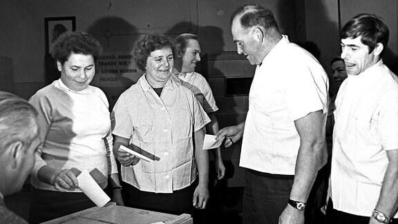 """Melker der LPG """"Neuland"""" stehen mit ihrem Chef 1971 an der Wahlurne"""