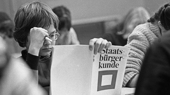 """Ein Schüler liest im Unterricht in einem Lehrbuch """"Staatsbürgerkunde"""""""