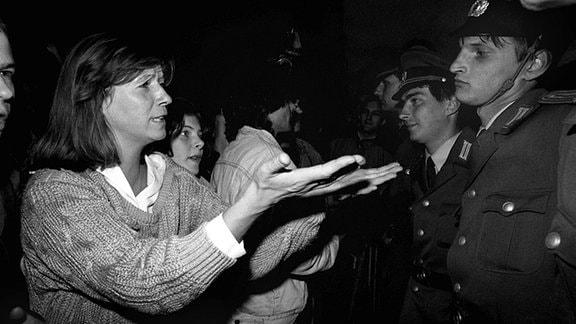 Mit einer Geste versucht eine Frau am 7. Oktober 1989 bei einer Demonstration in Ostberlin Beamte in einer Polizeikette von ihrer Friedfertigkeit zu überzeugen. Am 7. Oktober 1989 kam es wie in anderen ostdeutschen Städten auch in Ostberlin zu Demonstrationen gegen die Machthaber in der DDR.