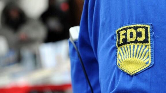 Ein FDJ-Aufnäher auf einem blauen Hemd