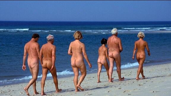 FKK-Anhänger laufen den Strand entlang