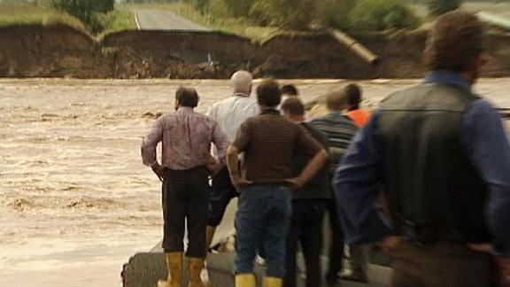Männer stehen am Fluss.