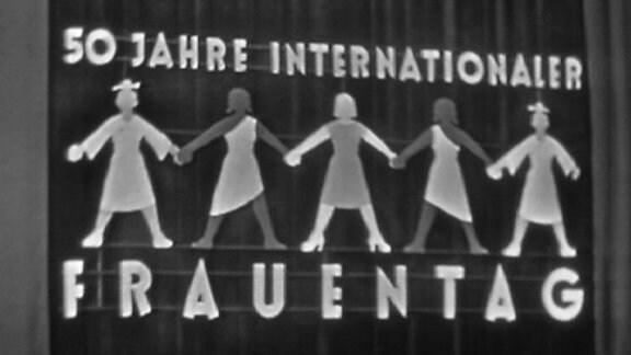"""""""50 Jahre internationaler Frauentag"""" steht auf einer Leuchtreklame"""