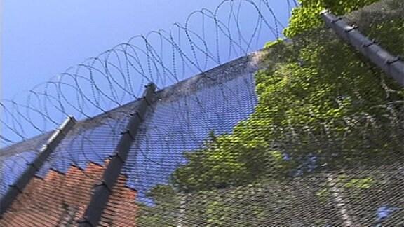 Ein hoher Zaun mit Stacheldraht.