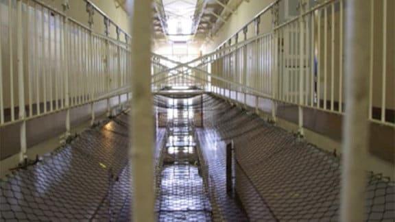 Ein Gefängnis im Inneren mit Zäunen und Fluren.