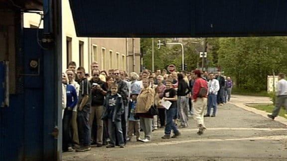 Menschen stehen in einer Schlange an.