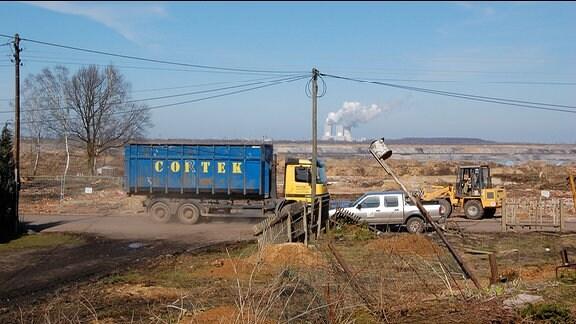 LKW fahren auf einer Brachfläche.