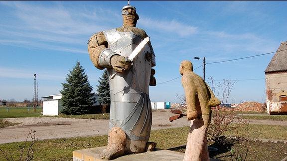 Zwei Plastiken aus Holz. Eine Riese und ein kleiner Mann stehen sich gegenüber.
