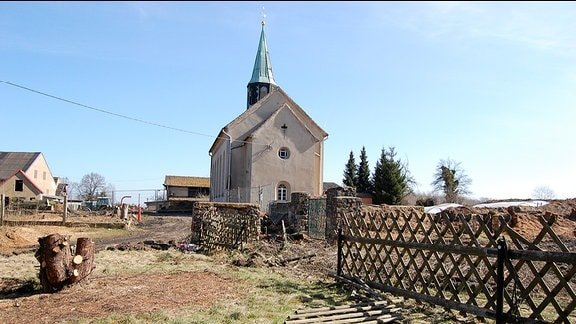 Kirche auf einer brachigen Fläche.