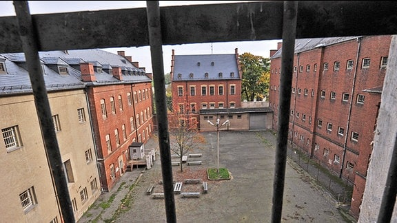 Blick durch ein vergittertes Fenster auf den Innenhof des ehemaligen DDR-Frauenzuchthauses Hoheneck im sächsischen Stollberg