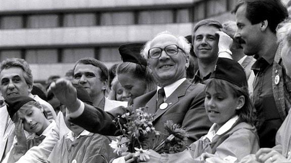 Erich Honecker (Mitte), Generalsekretär des ZK der SED und Vorsitzender des Staatsrates der DDR, Egon Krenz (l) und Eberhard Aurich (r) mit Pionieren auf der Ehrentribüne bei VIII. Pioniertreffen im August 1988 in Karl-Marx-Stadt.