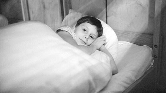 Jugendlicher in seinem Bett im Jugendwerkhof Wolfersdorf