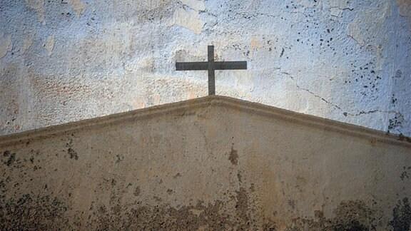 Auf eine rissige Häuserwand wurde ein Kirchedach mit einem Kreuz gezeichnet.