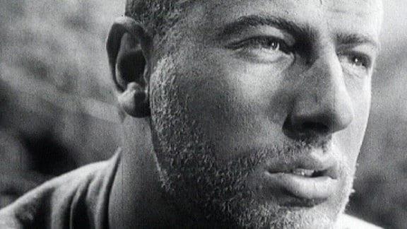 (Filmszene) Manfred Krug bärtig in Nahaufnahme.
