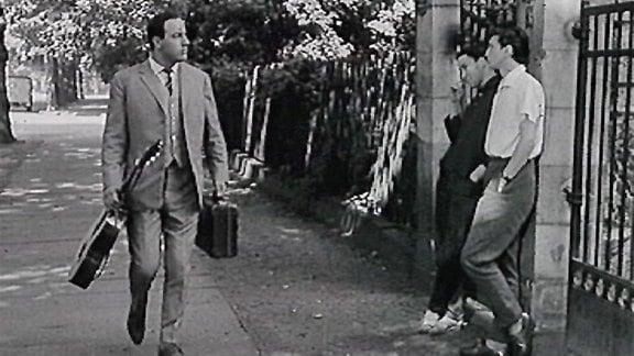 (Filmszene) Manfred Krug spaziert mit Gitarre und Koffer in der Hand an Pärchen in Toreingang vorüber.