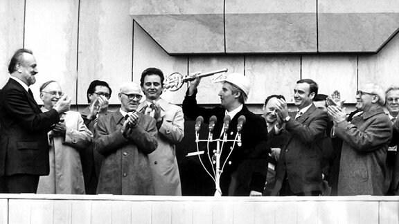 In Anwesenheit des Staatsratsvorsitzenden Erich Honecker (r) übergibt Obermeister Manfred Friedrich (M) am 8. Oktober 1981 unter dem Beifall von zehntausenden von Bürgern der Messestadt symbolisch den Schlüssel an Gewandhauskapellmeister Professor Kurt Masur (l).