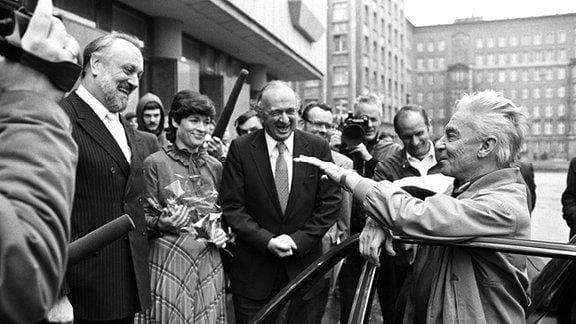 Der Leipziger Gewandhauskapellmeister Kurt Masur (l) begrüßt freudig den österreichischen Dirigenten Herbert von Karajan (r) vor dem Neuen Gewandhaus in Leipzig, aufgenommen im November 1981.