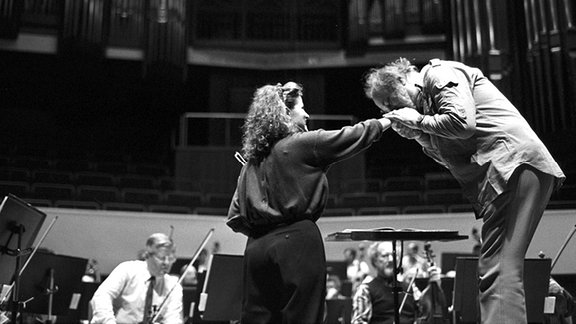 Der Dirigent des Leipziger Gewandhausorchesters Kurt Masur gibt der Geigerin Anne-Sophie Mutter während einer Orchesterprobe einen Handkuß, aufgenommen 1988.