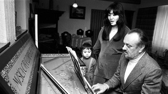 Der Dirigent des Leipziger Gewandhausorchesters Kurt Masur in Familie bei der Hausmusik - Masur begleitet den Gesang seiner Ehefrau Tomoko mit dem Spiel auf dem Cembalo, ihr gemeinsamer Sohn Ken-David hört interessiert zu.