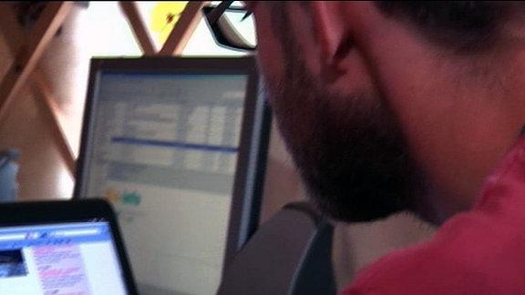 Ein Mann vor zwei Bildschirmen