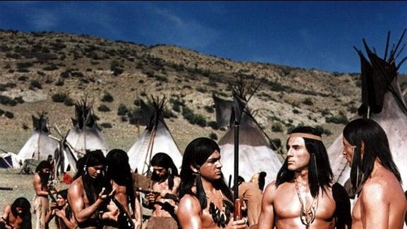 Nachdem Weiße einige Stammesmitglieder getötet haben, hat Häuptling Weitspähender Falke (Gojko Mitic, 2. v. rechts) Gewehre besorgt, um die Toten zu rächen. Die Krieger lernen ihre neuen Waffen kennen.