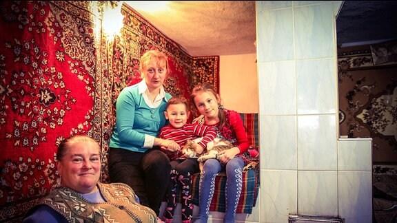 Frau mit Kindern vor Wandteppich