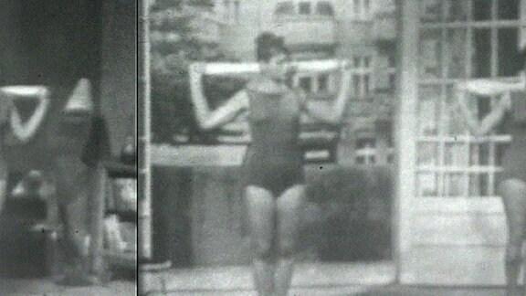 Sportübung einer Frau im Gymnastikanzug mit gerolltem Handtuch hinterm Rücken.