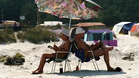 Ein Ehepaar sitzt nackt lesend auf dem FKK-Zeltplatz Prerow auf dem Darß, Rücken an Rücken, unter einem Sonnenschirm.
