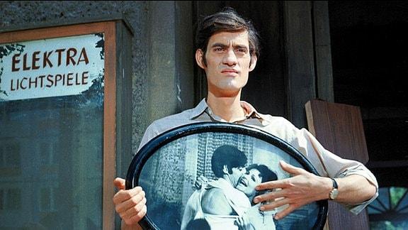 Paul (Winfried Glatzeder) steht mit einem Erinnerungsfoto von ihm und Paula (Angelica Domröse) vor Paulas Haus