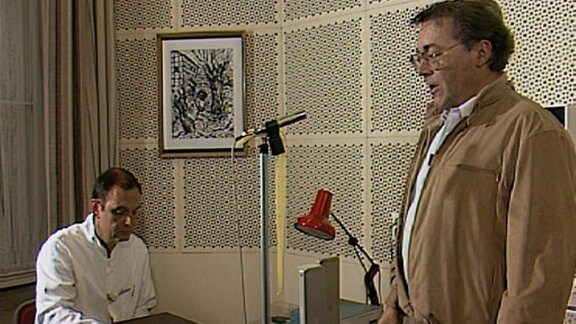 Ein Mann steht vor einem Mikrofon, ein anderer sitzt an einem Aufnahmegerät