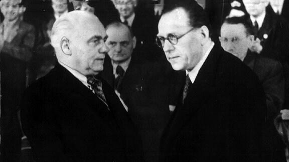 Das Bild zeigt den symbolischen Händedruck zwischen dem KPD-Vorsitzenden Wilhelm Pieck (l) und dem SPD-Vorsitzenden Otto Grotewohl (r) auf dem sogenannten Vereinigungsparteitag im Berliner Admiralspalast