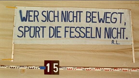 """Plakat mit dem Zitat: """"Wer sich nicht bewegt, spürt seine Fesseln nicht"""""""