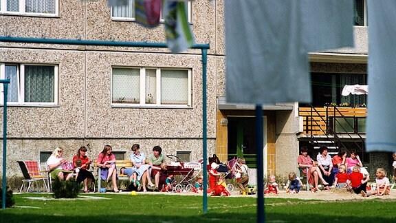 Vor einem Plattenbau im früheren Ostberliner Stadtbezirk Hellersdorf sitzen im Jahr 1985 junge Frauen auf Klappstühlen und Bänken und sind in Gespräche vertieft, während ihre Kinder im Sandkasten und auf der Wiese vor dem Wohnblock in der Sonne spielen.