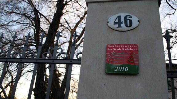 Ein Pfosten, auf dem eine Hausnummer und eine Plakette angebracht sind.