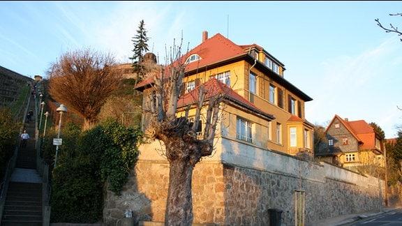 Die Abendsonne scheint auf ein dreietagiges Haus mit einem roten Dach. Unter dem Haus befindet sich eine sehr hohe Mauer, links neben dem Haus führt eine Treppe durch Weinberge.