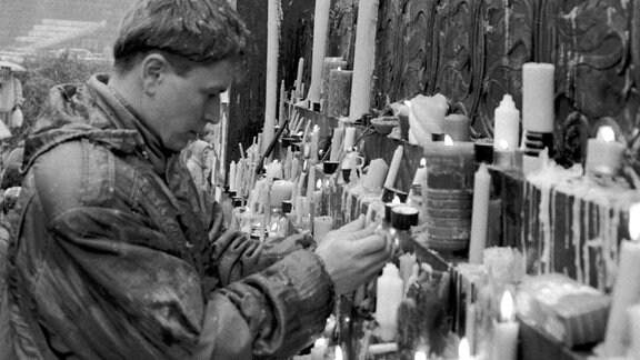Menschen stellen Kerzen auf.