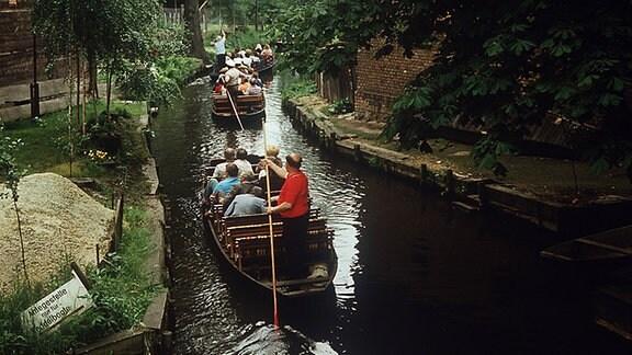 Touristen in Kähnen auf einem Kanal im Spreewald.