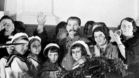Josef Stalin auf einer Konferenz mit Ehefrauen des Führungsstabes und deren Kindern. (1935)