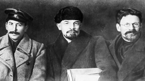 Wladimir Iljitsch Lenin zwischen Josef Stalin und Michail Kalinin, anlässlich des 8. Parteitages der Kommunistischen Partei Russlands (Bolschewiki) in Moskau (1919).