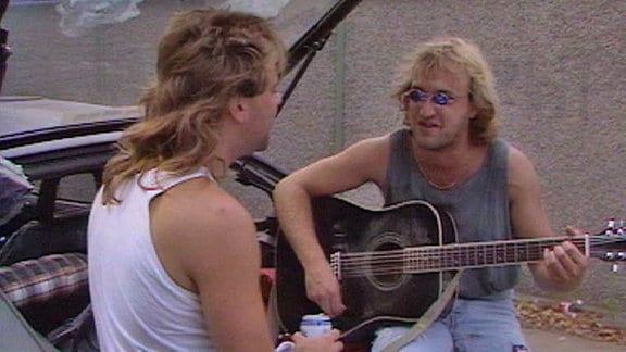 Zwei langhaarige Männer in Muskelshirts, einer mit Gitarre und zerrissener Jenas, sitzen am Heck eines Autos.